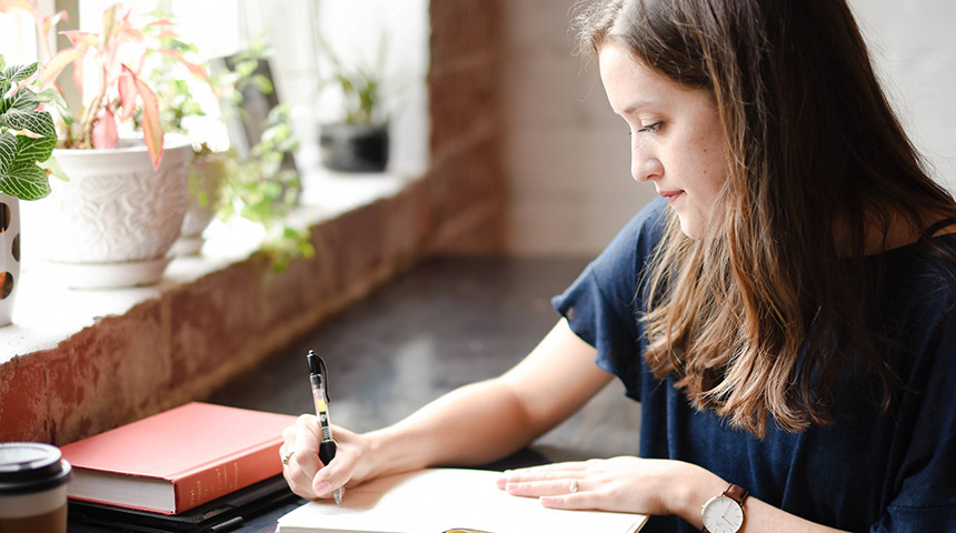 Girl studying and writing notes in a cafe