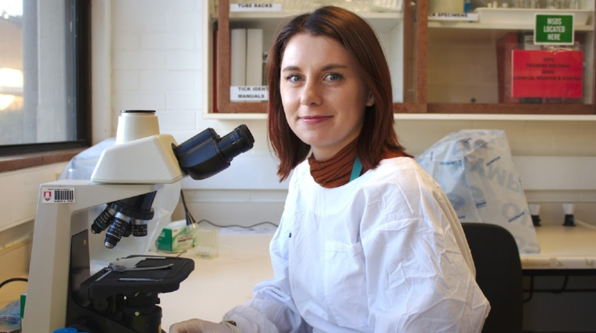 Siobhon Egan sitting next to a microscope in the lab