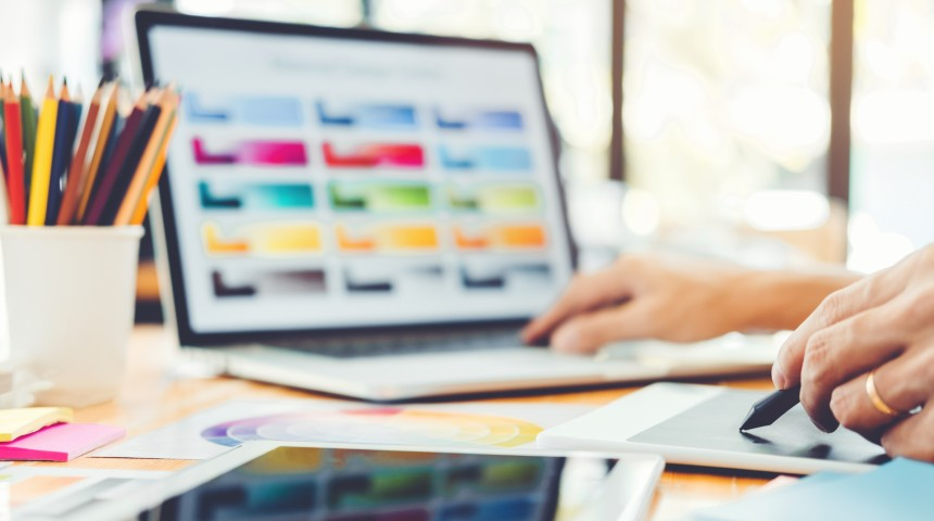 Graphic designer at work behind a laptop