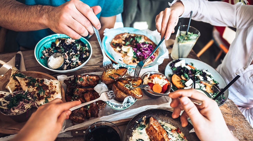 Friends gathered around a table with vibrant food