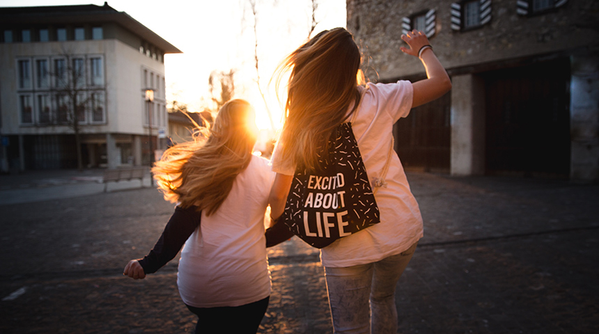 Two girls skipping into the sunset