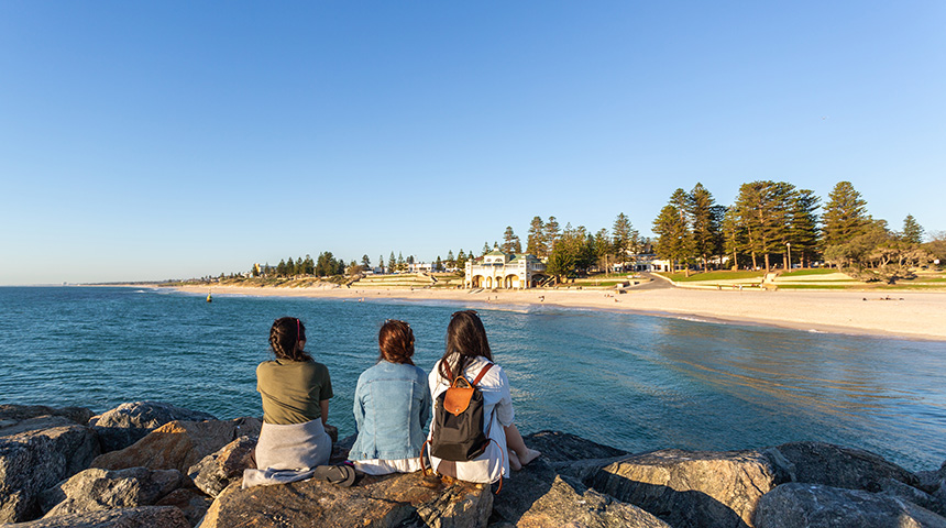 Three female students sitting with their backs to the camera on the groyne at Cottesloe beach with the Indiana Teahouse in the background.