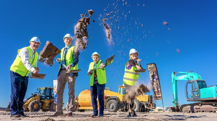 Four people throwing soil from spades at construction site of new food facility