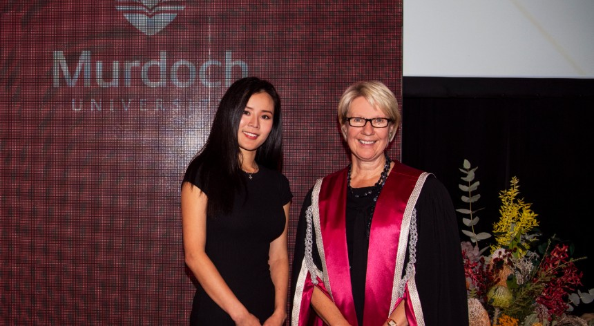 Wenna Lee and Vice Chancellor Eeva Leinonen stand in front of a banner at the VC awards