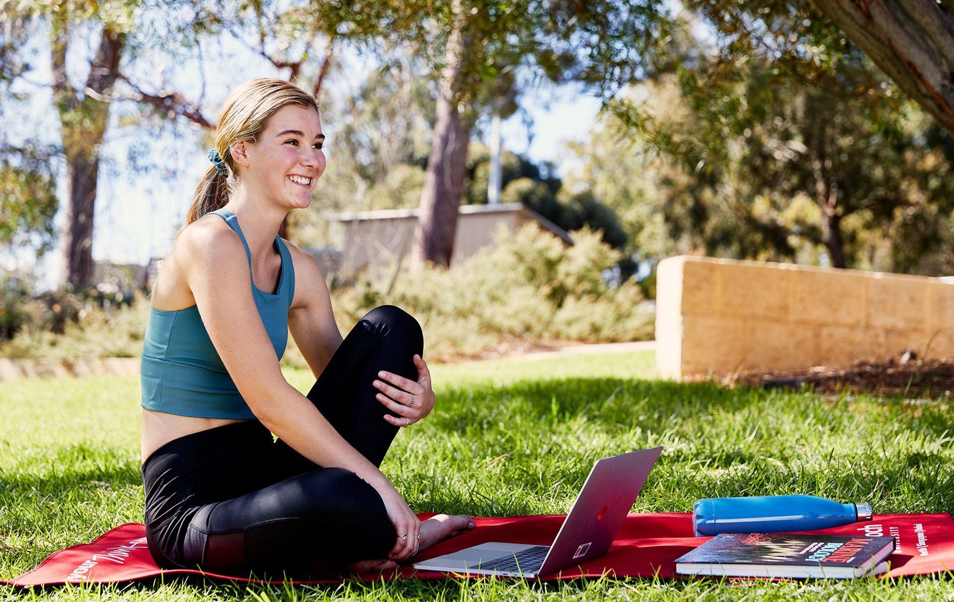 Gabby studying outside on a yoga mat