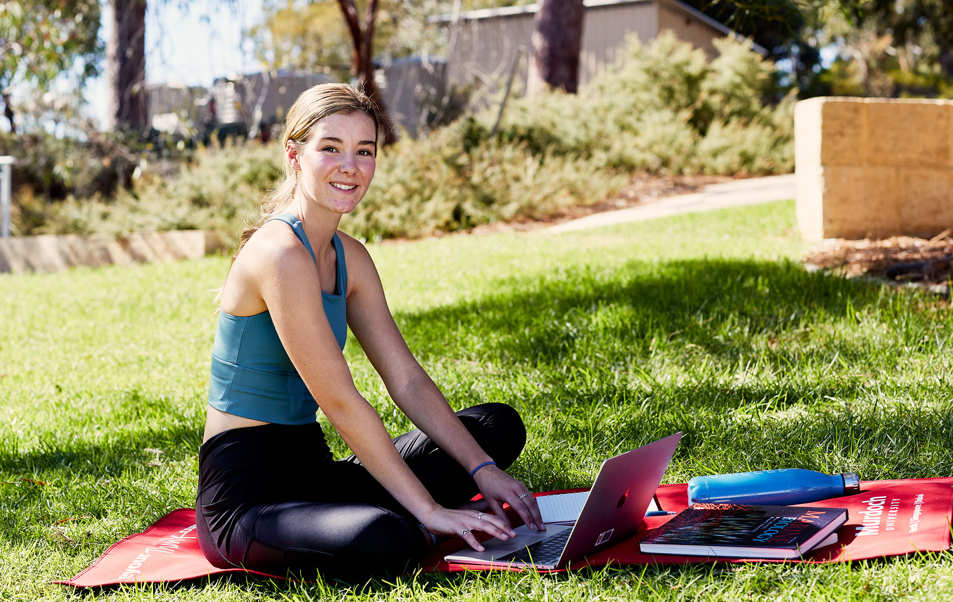 Gabby studying on her laptop while sitting on a yoga mat