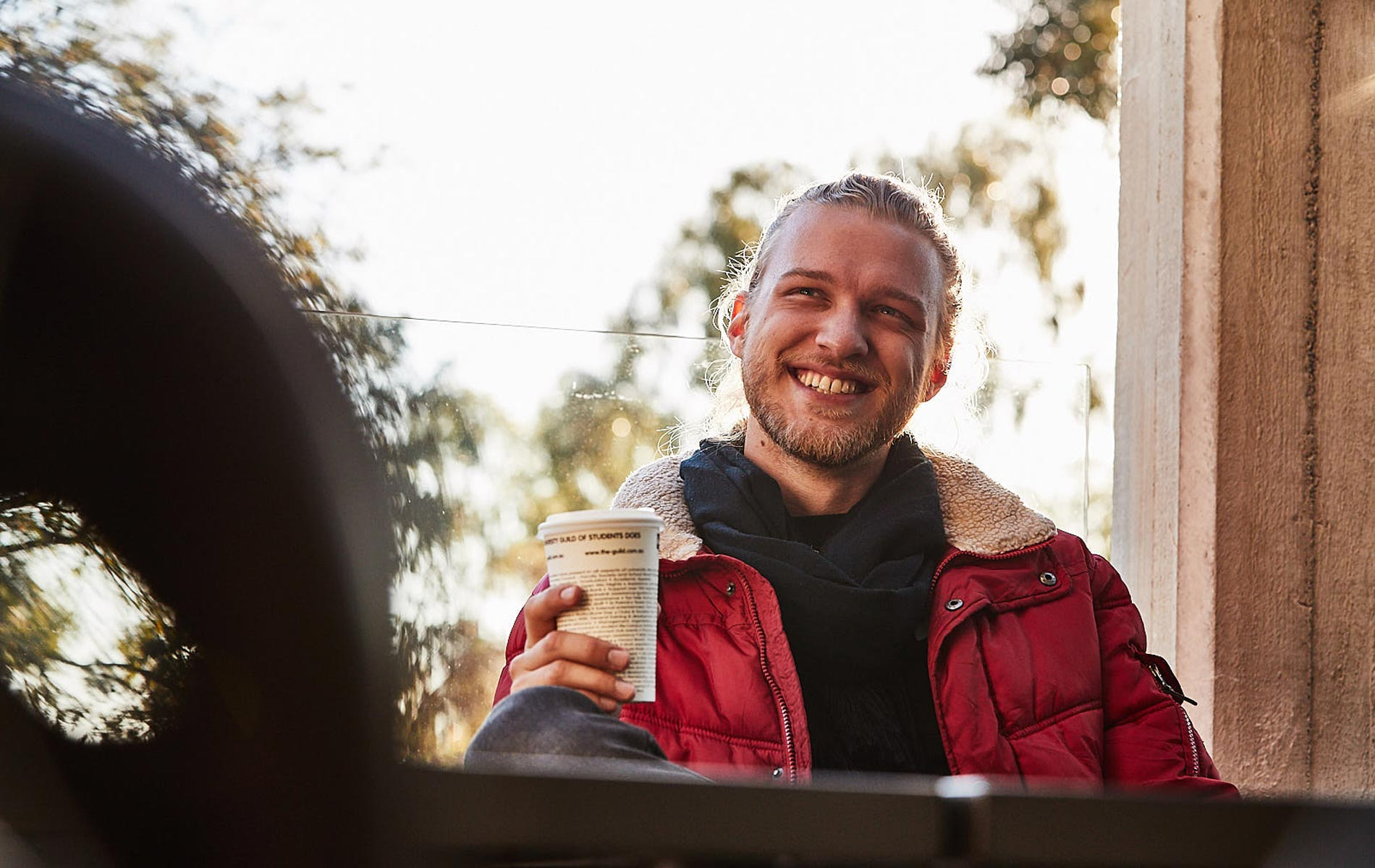 Murdoch student James Norton having a coffee while smiling on campus
