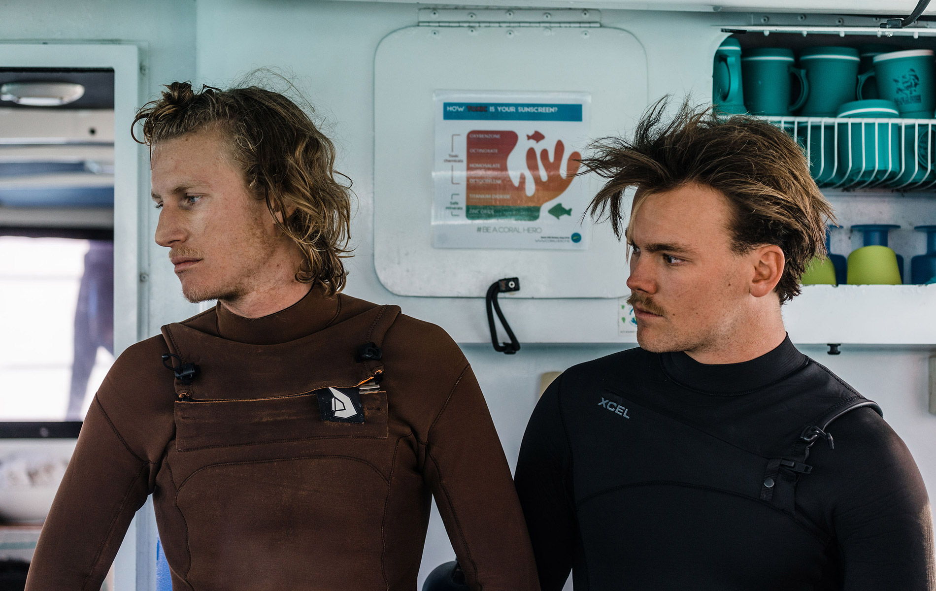 Two men in wet suits on a boat