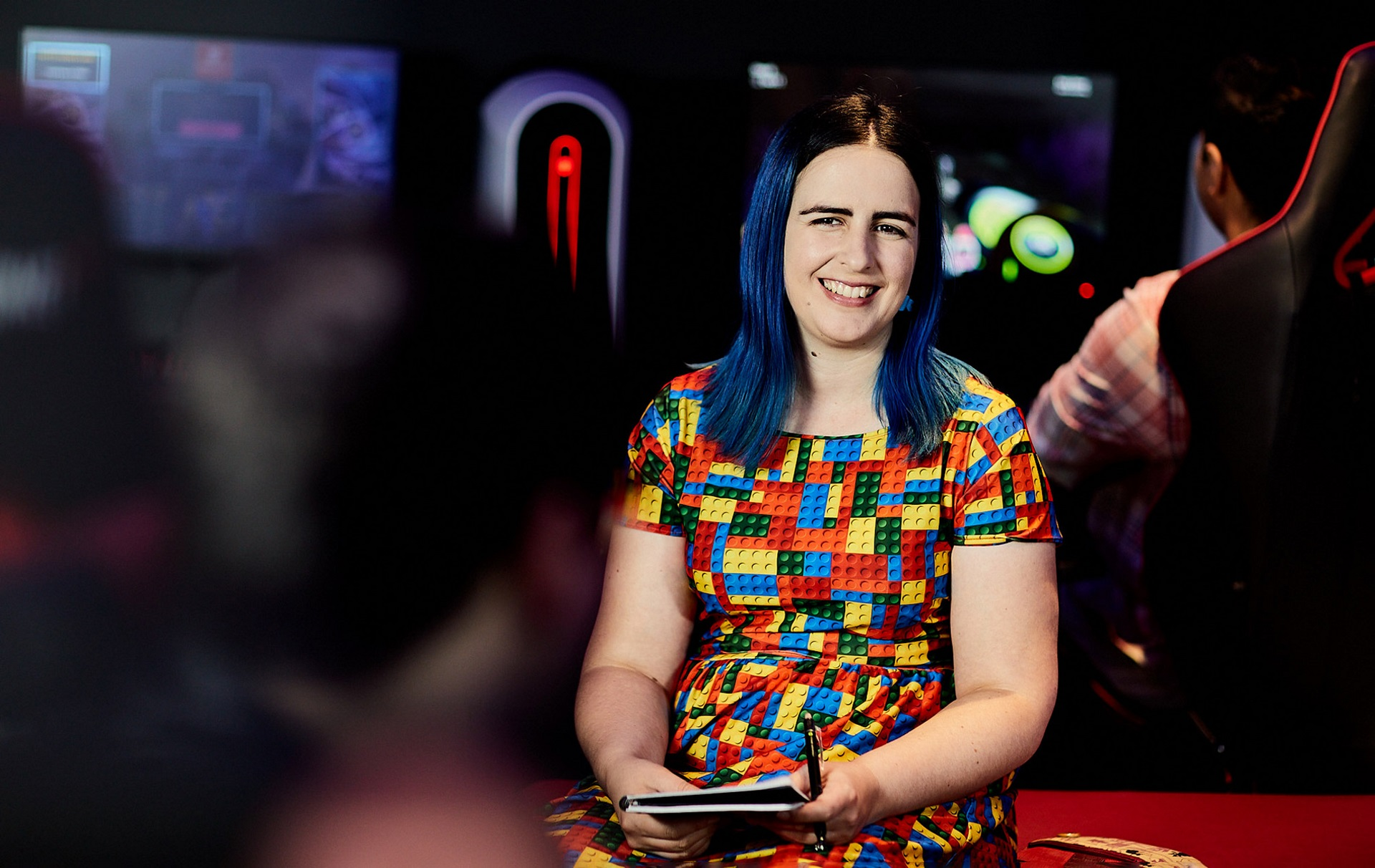 Megan sitting in the esports hub with a notepad