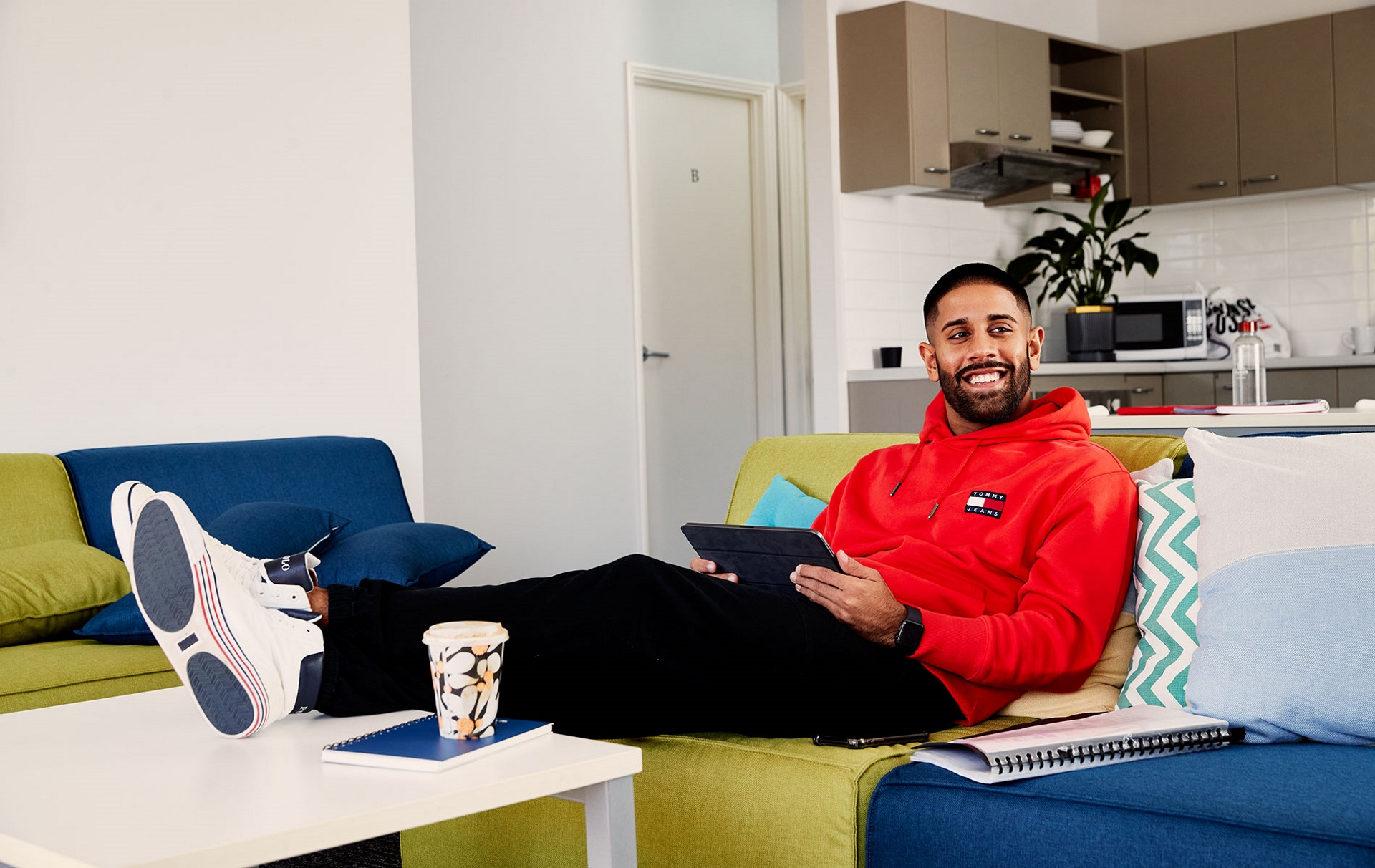 Murdoch student Nikhil sitting on a couch smiling