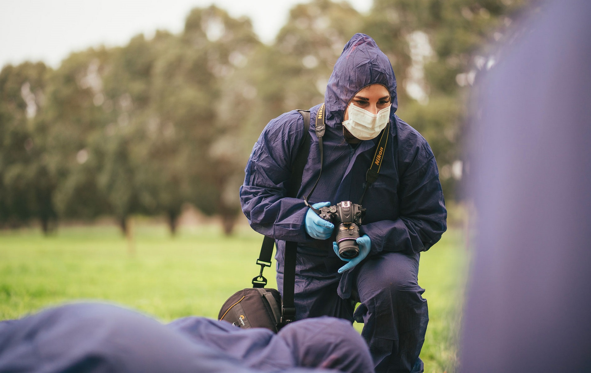 Rebecca holding a camera and wearing coveralls at a crime scene