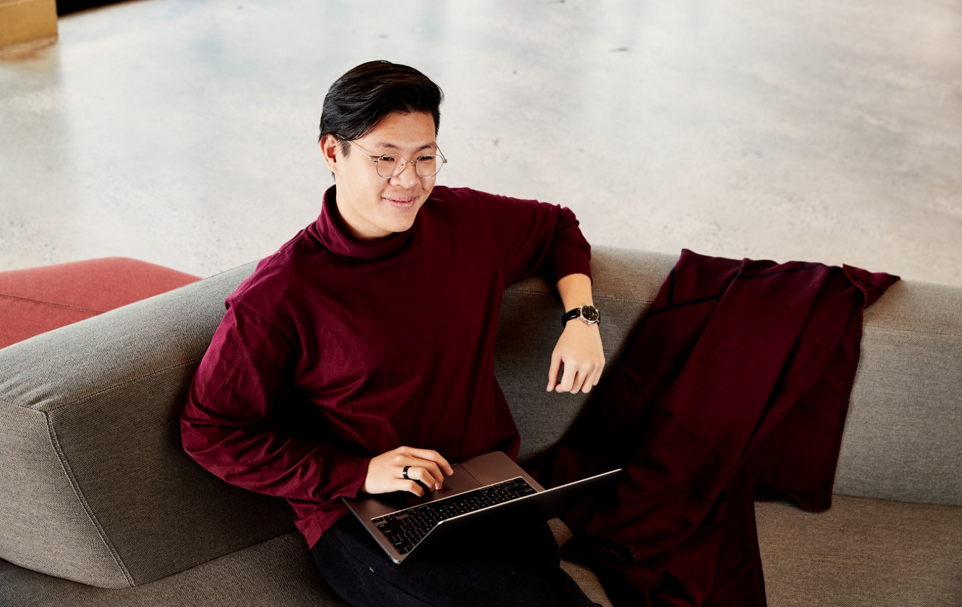 Tien sitting on couch with laptop