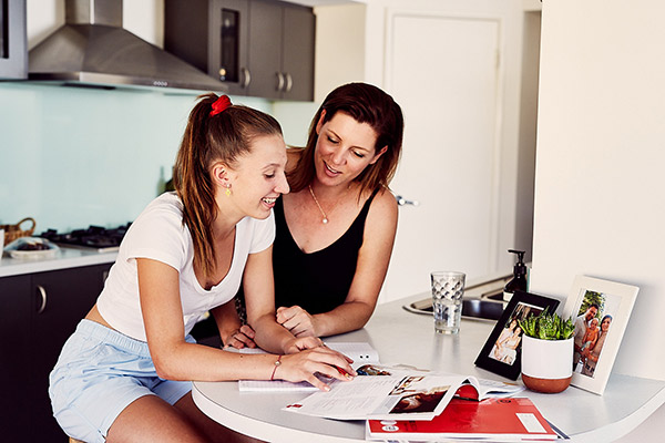 Mother and daughter sitting at kitchen bench