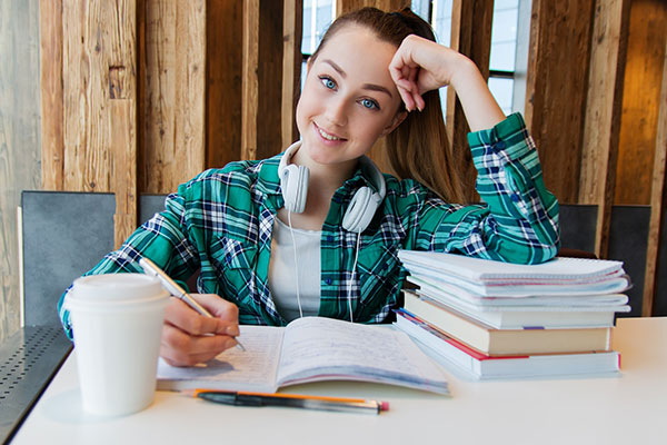Young girl sitting at desk with notebook, books, and coffee