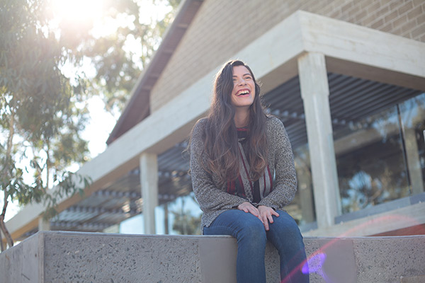Female student sitting on a wall smiling
