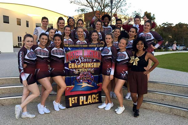 18 members of the Murdoch University Cheerleading Team in uniform, smiling and posing with a 1st place banner