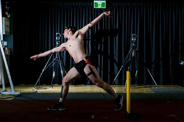 Cricket player bowling with electrodes attached for gait analysis