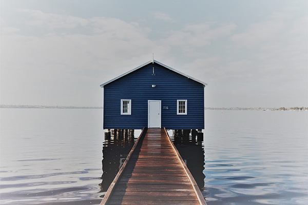 Blue boathouse with jetty surrounded by water and sky