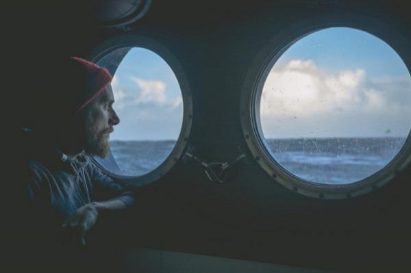 Man looking out window of ship