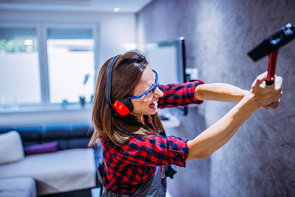 Woman smashing wall with tool