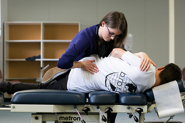 Female chiropractor performing adjustment on male patient