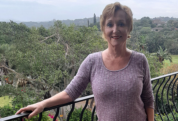 Cynthia stands on her balcony overlooking the green South African jungle