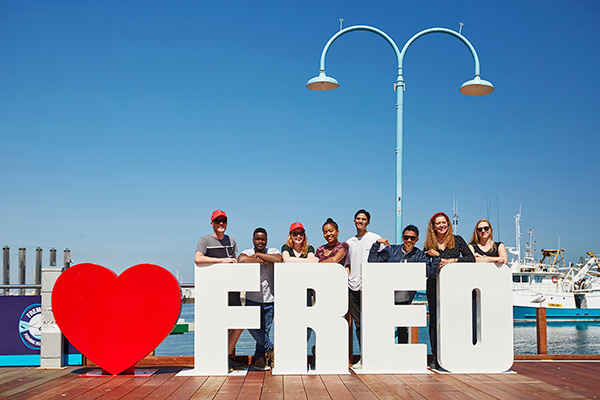 Group of smiling students standing behind a 'love freo' sign on habour in Fremantle