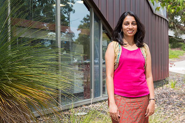 Student Deepa Machaiah posing and smiling outside building and grass tree at Murdoch