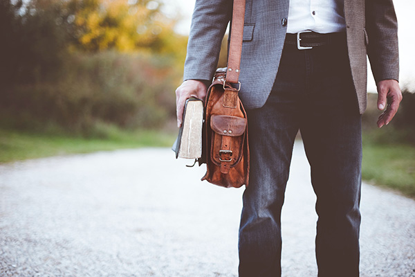 Man holding a briefcase and book