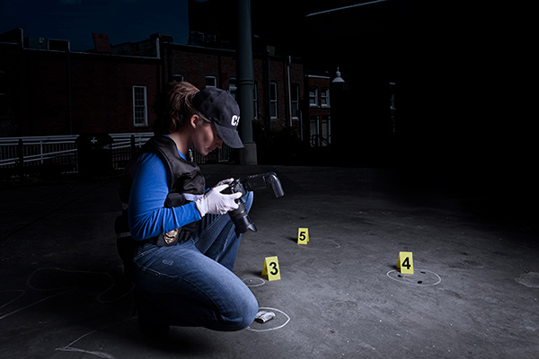 Forensic student examining crime scene with camera