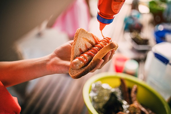 Image of person's hand holding piece of bread with barbecued sausage
