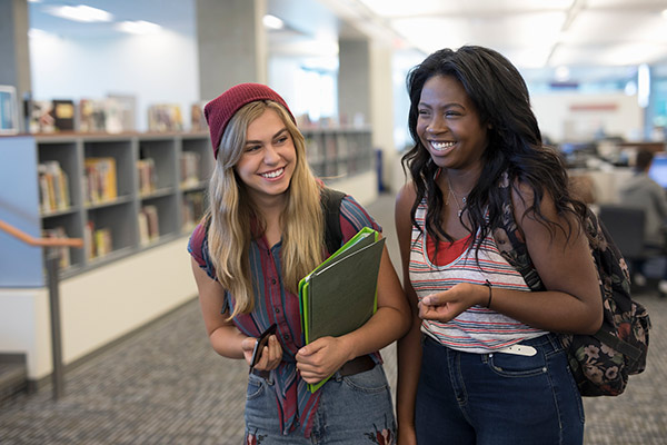 Two girls laughing in a library