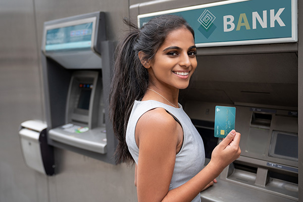 Female student smiling in front of ATM holding up a debit card