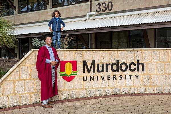 Huthayfa in front of Murdoch sign on graduation day