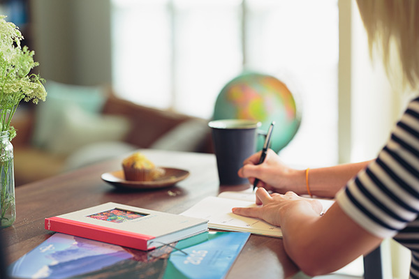 Thumbnail image of woman sitting at a desk writing in a notebook