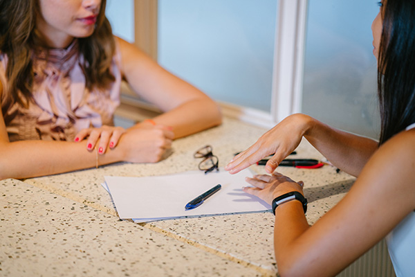 two women sit at a table with a pen and paper between them