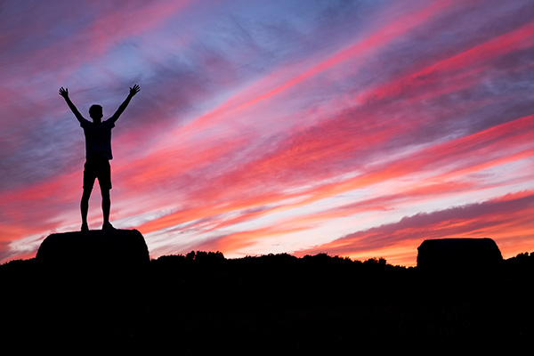 Silhouette of person standing at the top of a mountain with their arms in the air