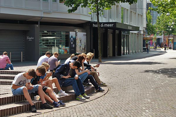 Group of teenagers sitting outside using their phones