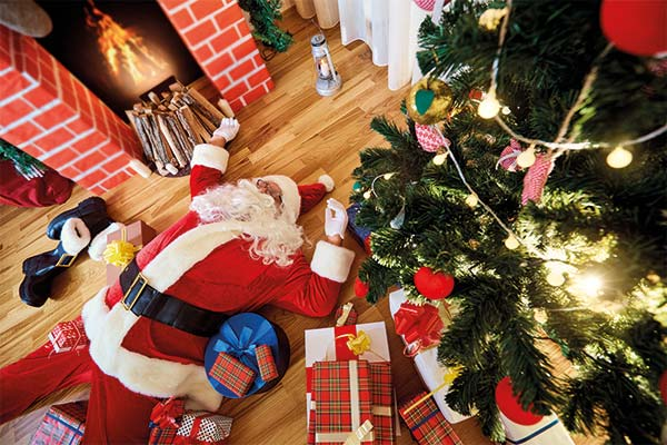 Stressed santa lying amongst presents
