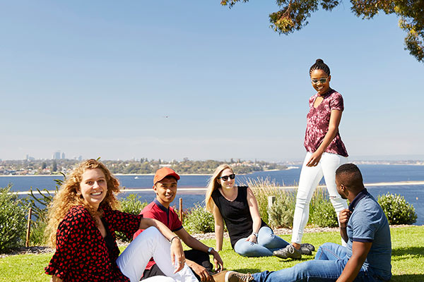 A mix of students smiling and sitting at Kings Park with the Perth CBD in the background